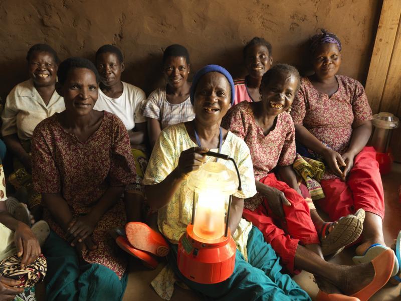 Women hold up solar lanterns in Malawi