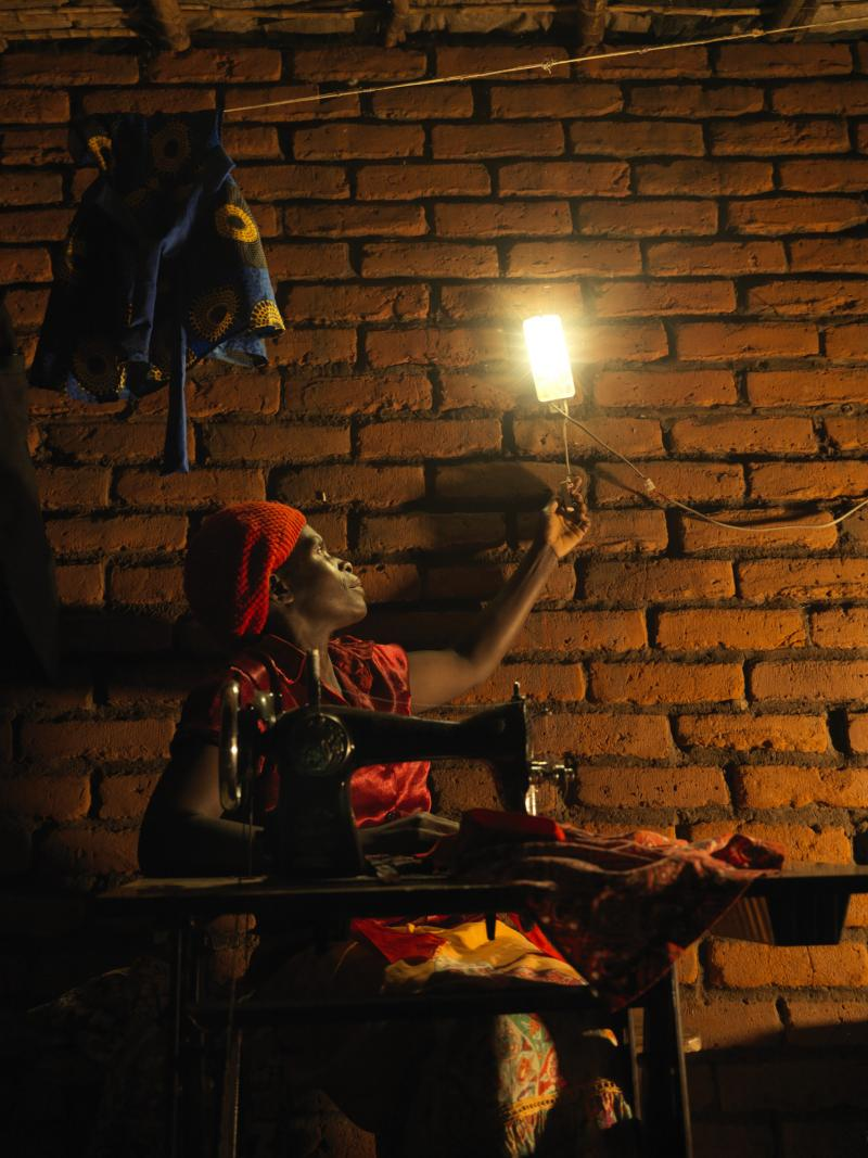 Seamstress works by solar lamp at night in Malawi