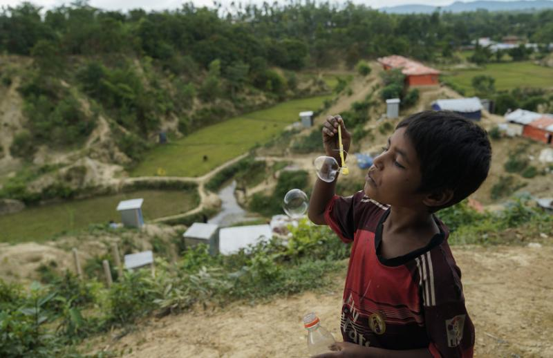 A boy blows bubbles against the backdrop of the Rohingya refugee camps at Jamtoli, Cox's Bazar, Bangladesh