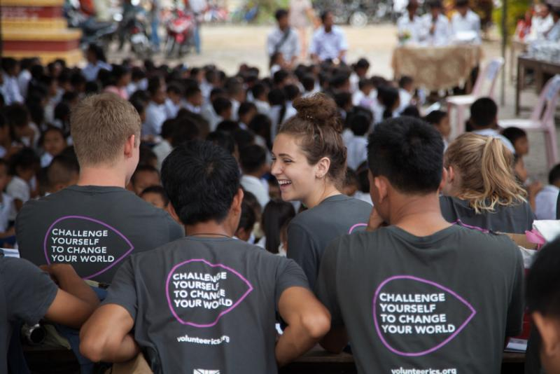 ICS volunteers sit in front of a big group of children in Cambodia