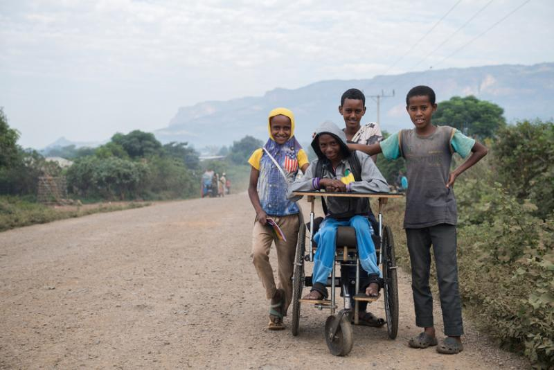 boy in wheelchair with three friends on a road that are helping to push him
