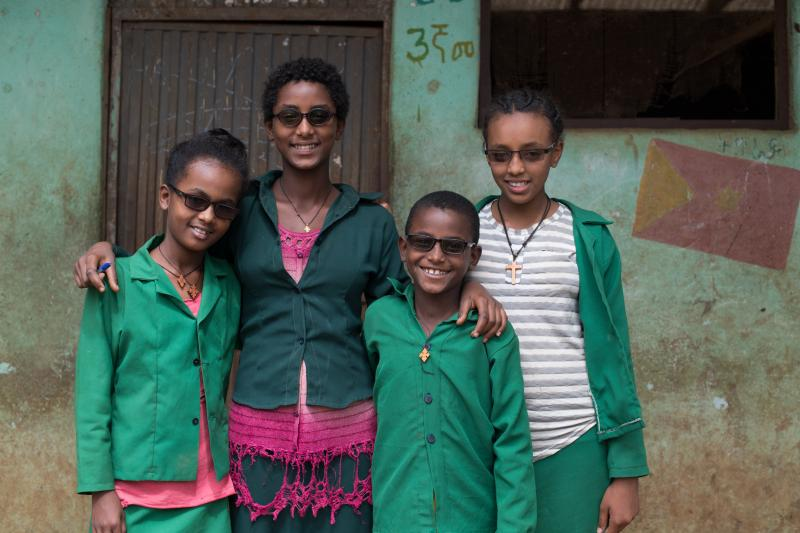 four children stood outside a building wearing tinted glasses
