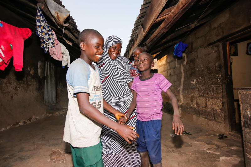 Fatima playing with her children by her home in Niger State, Nigeria.