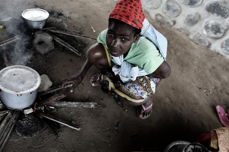 A woman cooking under a bridge in Beira