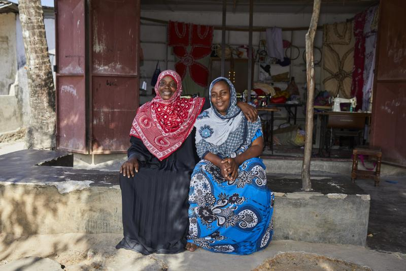 Tailors Tatu and Namboto sit on a step outside their sewing workshop