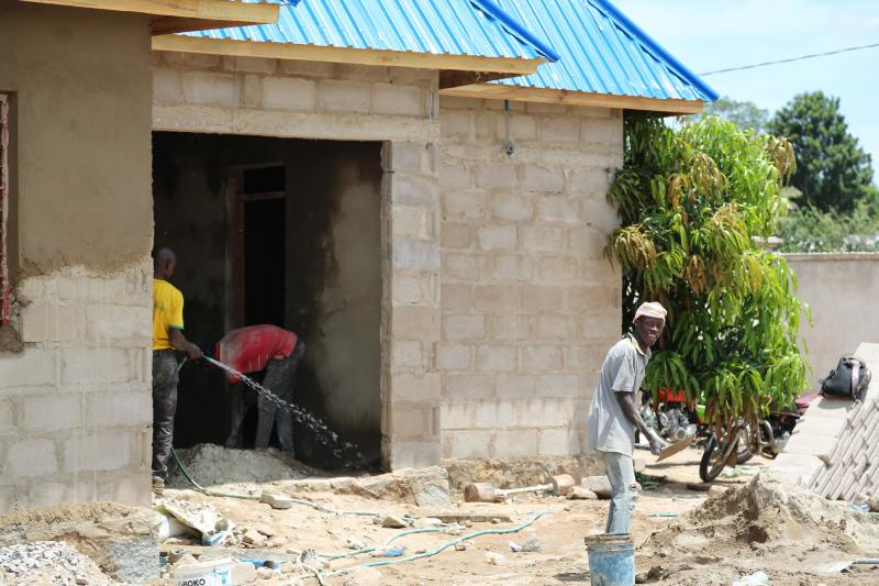 Builders work on a new outbuilding with a bright blue roof
