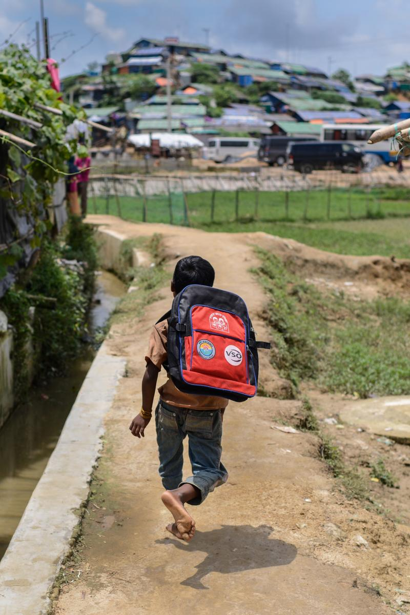 A Rohingya child runs with their new VSO backpack, filled with school supplies, so they can begin to learn the basics of education.