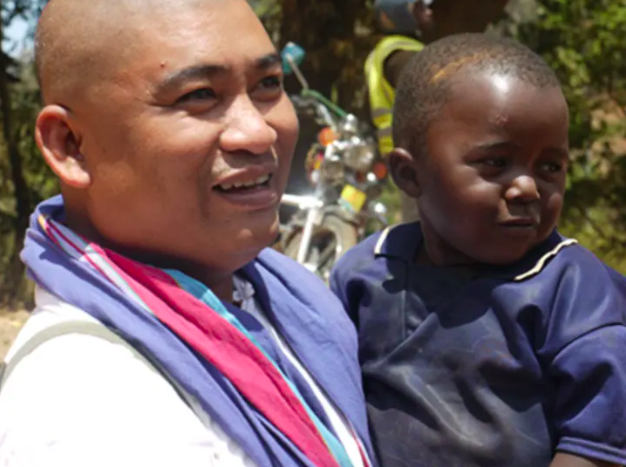 Juanito Estrada, pictured here with a child, has been a full-time volunteer for ten years.