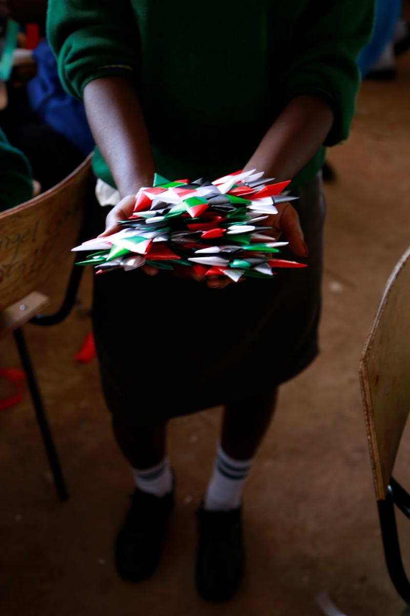A girl carries a handful of stars woven from ribbon by young people in workshops in Nairobi