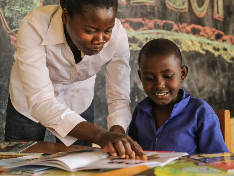 Alphonsine teaching Alice how to read a book using signs in Rwanda