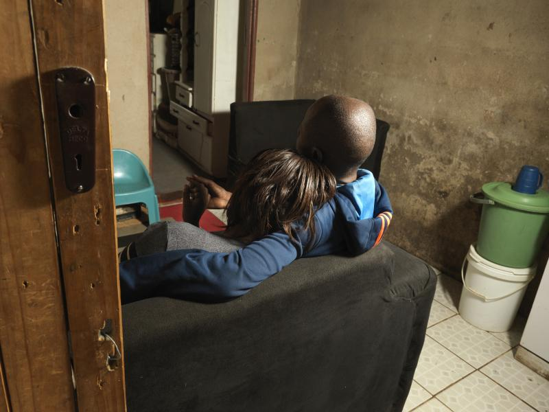 a couple sitting together on a sofa, from the back so faces cant be seen