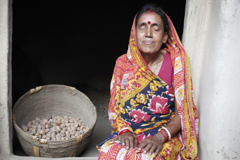 Blind woman farmer with potatoes supported by VSO in India