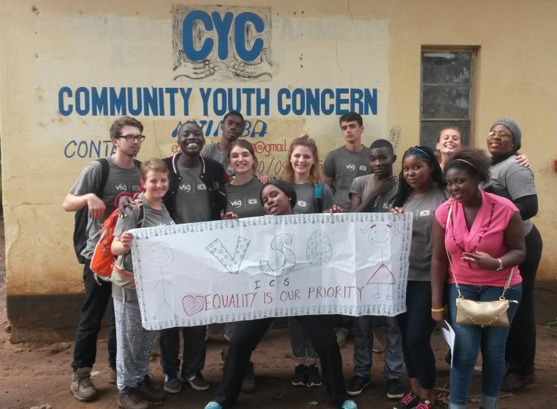ICS volunteers in Zambia stand holding a sign against a wall