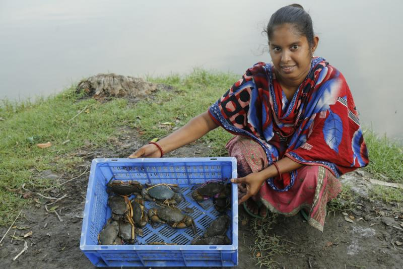 A woman next to a river showing crabs she has caught