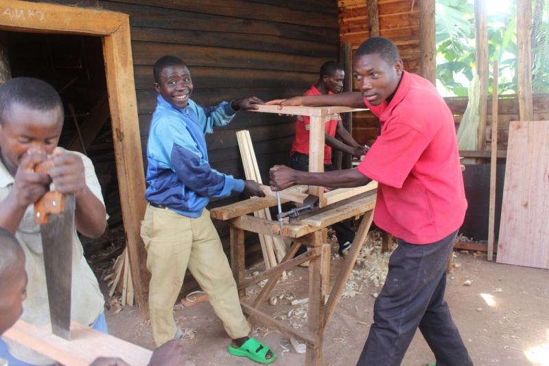 a group of rwandan men making furniture outside