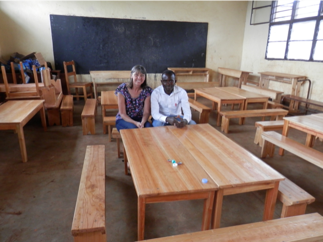 woman and man at in an empty classroom with desks and chairs