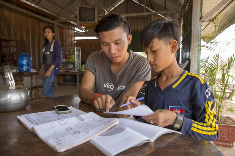 ICS volunteer Ratha Chea sits in a cafe helping a school child with his homework in the village of Banteay Char, near Battambang
